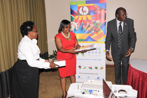 The TMEA Country Director, Ms Allen Asiimwe, and Ms Florence Kasule, Executive Director of AWEPON receive manuals developed by PSI Consult from the Team Leader, Mr George Egaddu